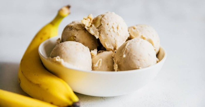 two bananas on a table with a cup full with banana ice cream balls
