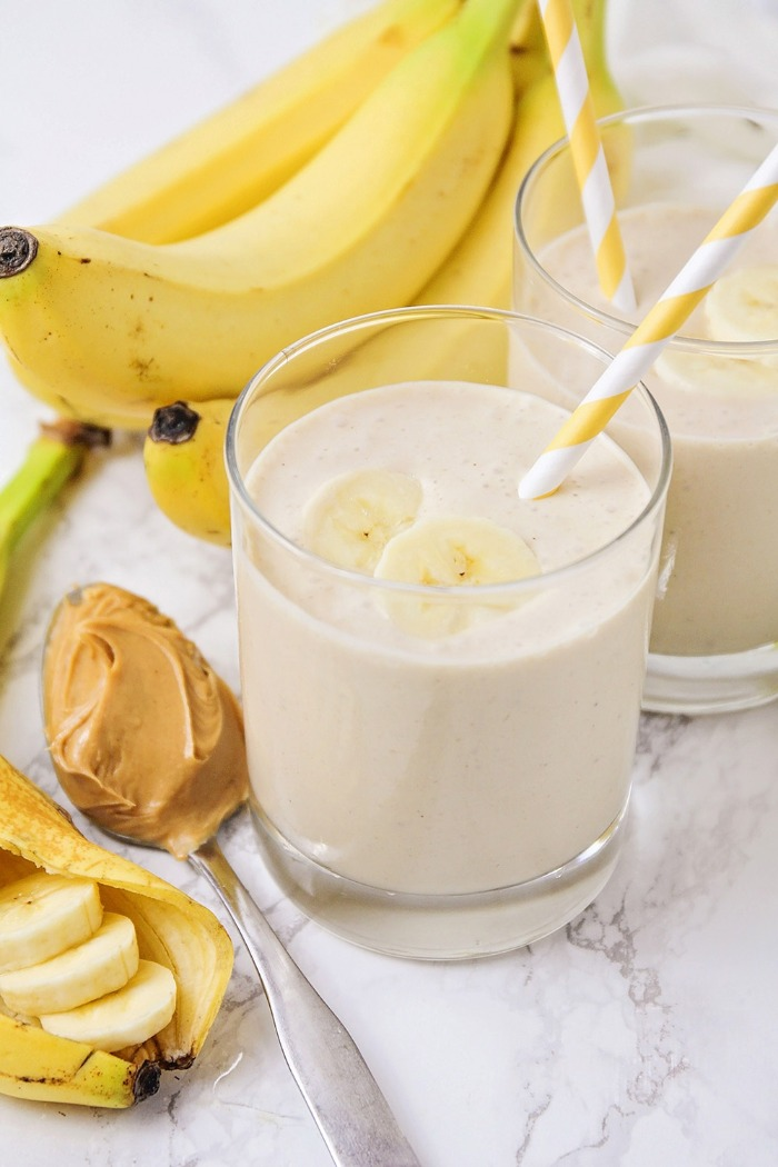 banana smoothie in a glass with a straw and bananas in the background spoon of peanut butter
