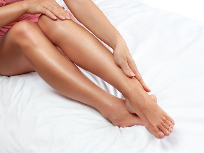 applying a bronzer on the legs on a white bed