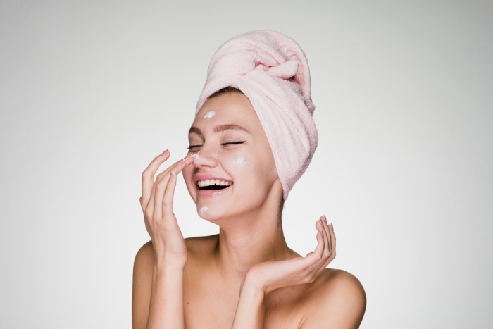 woman with a towel on her hair smiling and applying face cream