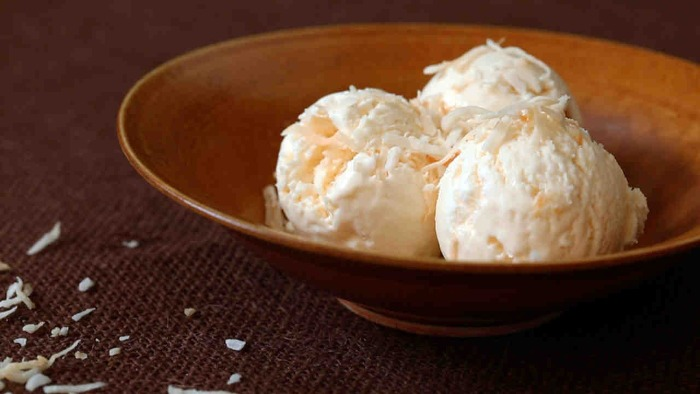 three balls of lactose free coconut ice cream in a brown bowl on a table