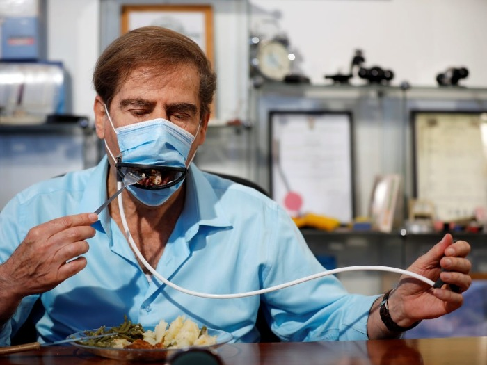 man in a light blue shirt demonstrating eating with the remote controlled face mask