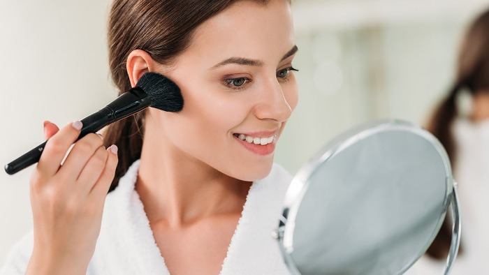 woman looking herself in the mirror using a black brush to apply bronzer on her face