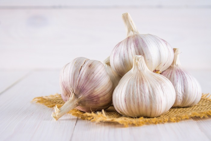 a small pile of garlic on a little burlap cloth white table top