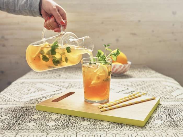 person pouring ginger ice tea with herbs in a glass on a table