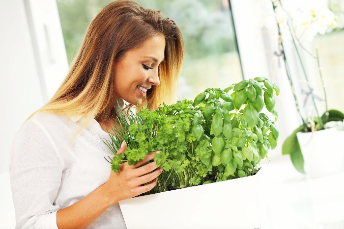 woman dressed in white bending over a pot of herbs smiling