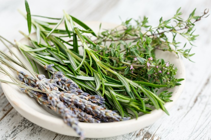 herb bouquet lavender rosemary and thyme branches in a white bowl on a wooden table