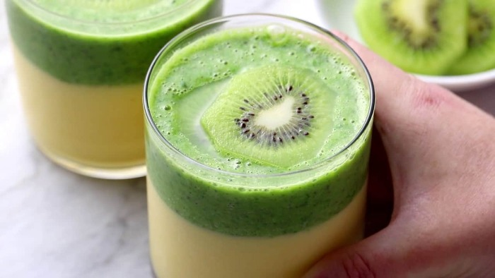 two color cooling kiwi smoothie in a glass with a piece of kiwi inside