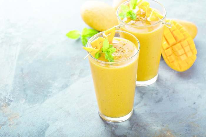 two bright yellow mango smoothies on a stone table top