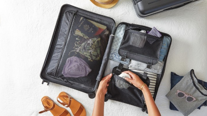 open suitcase hand packing sandals bags travel bag on the floor