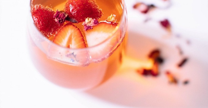 rose and strawberry ice tea in a glass on a white table