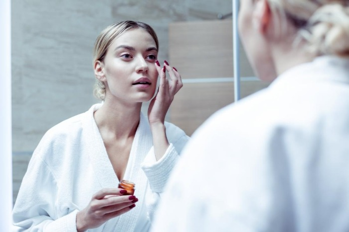 woman looking in the mirror applying hyaluronic acid on her face under her eyes