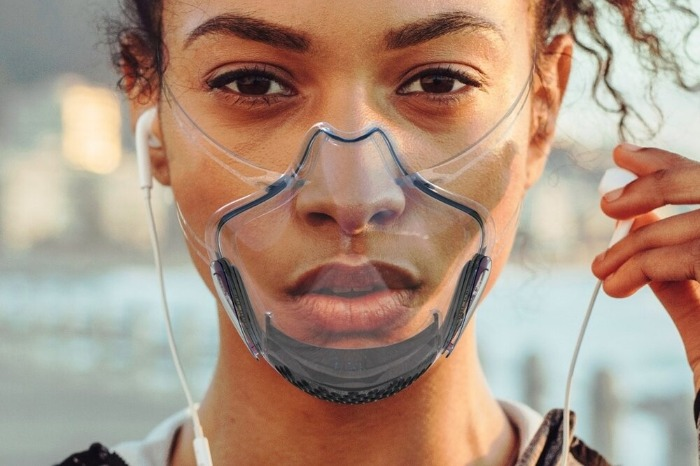 woman wearing a transparent face mask and headphones