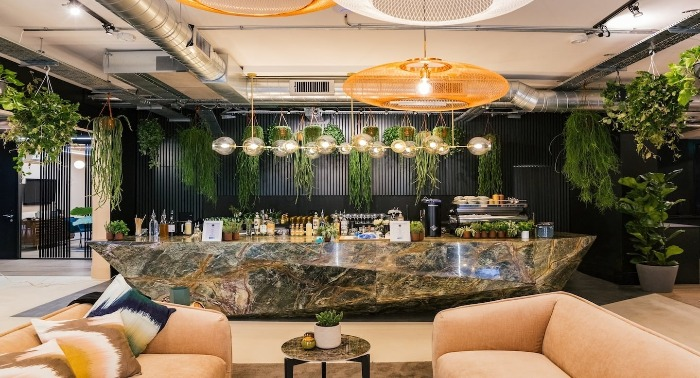 uncommon coworking space with comfortable sofas large stone bar living plants
