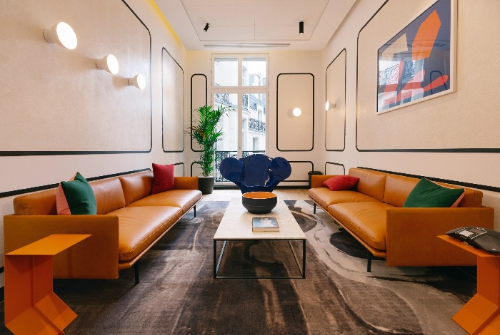 wework campus paris wooden floor leather sofas and bright colorful accents