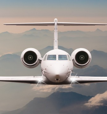 Airplane fly over clouds and Alps mountain on sunset. Front view of a big passenger or cargo aircraft, business jet, airline. Transportation and travel concept.
