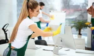 Young female worker cleaning office