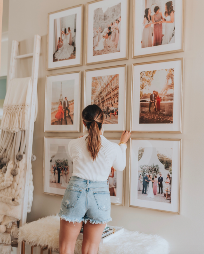 woman arranging posters on the wall on a wall in a room