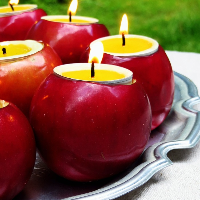 red apples with candles on a tray outside