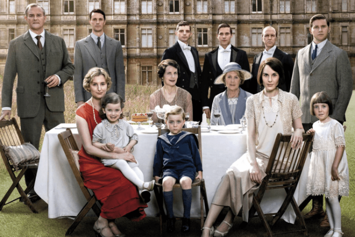 downton abbey cast in front of highcelere castle around a dining table outdoors