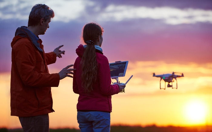 father teaching daughter how to fly a drone shooting sunset
