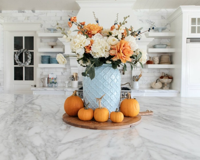 fall home decor ideas blue vase with white and orange flowers and pumpkins