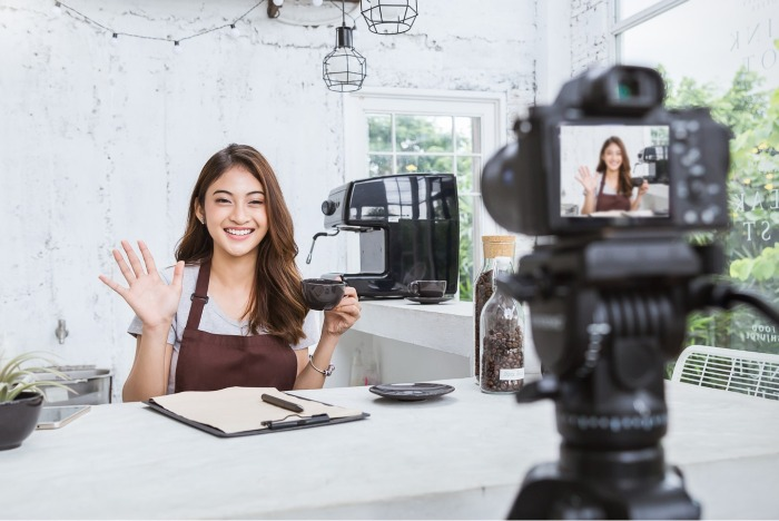 lifestyle influencer in apron waving at a camera set up with a cup of coffee