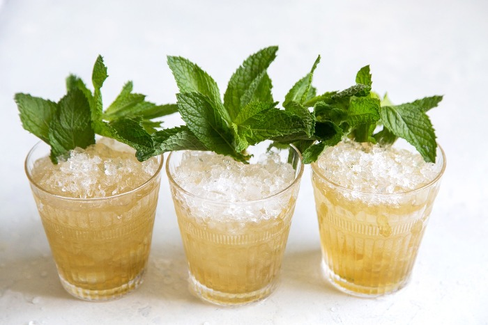 three mint julep cocktails with mint decoration with crushed iced