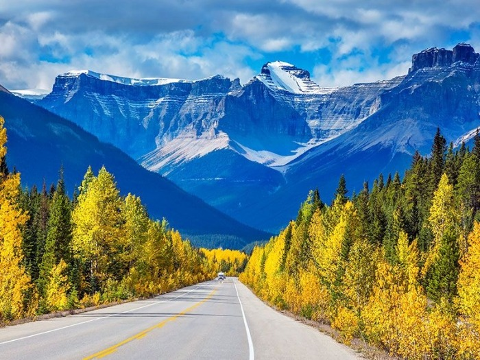 the rocky mountains canada in autumn road with snowy peaks in the background