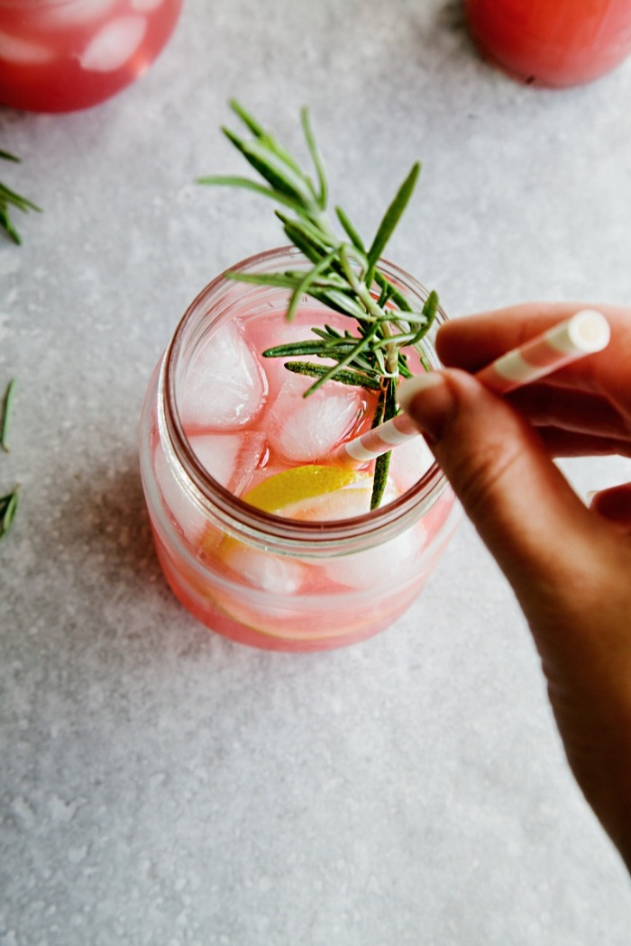 hand stirring a rosemary cocktail with a straw