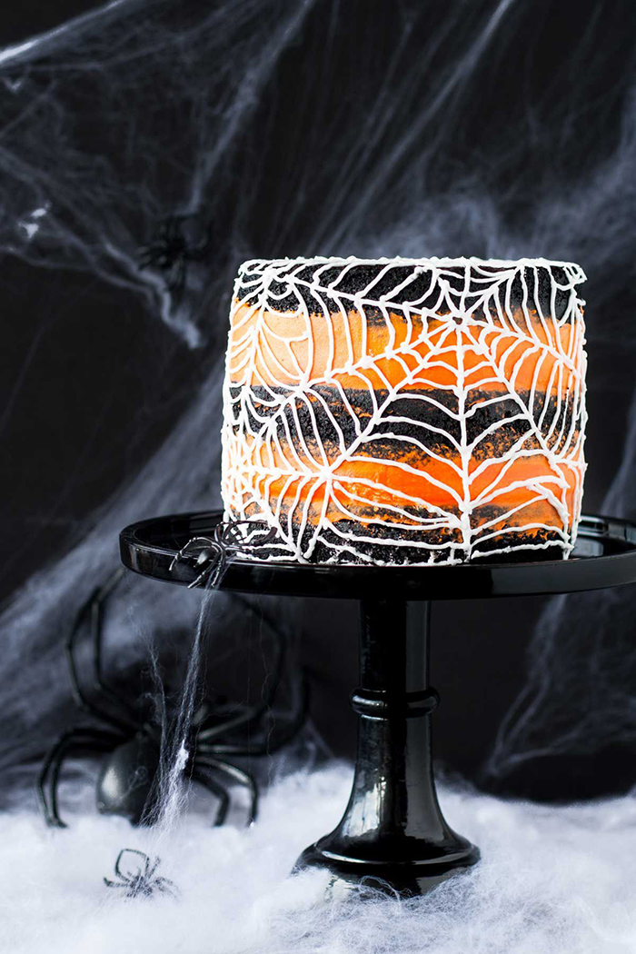 Halloween cake spider web with orange and black layers spider web in the background and a black spider