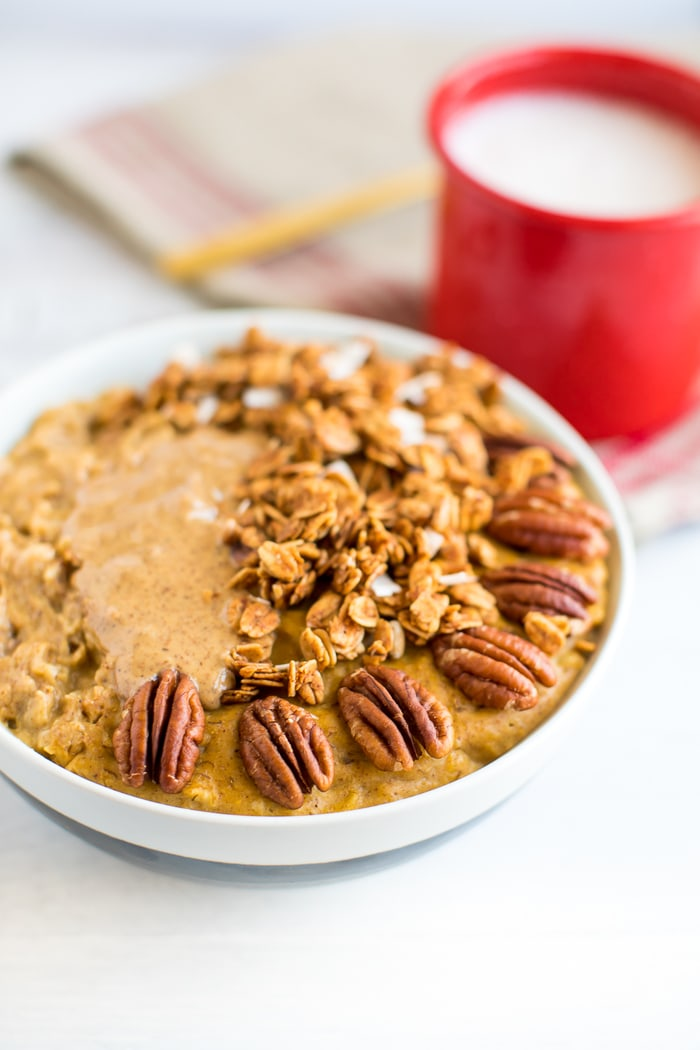 Best healthy breakfast ideas for the fall pumpkin oatmeal on a white table with red mug