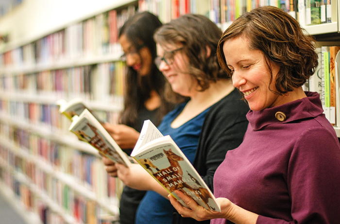 best new hobbies three women smiling and reading books at a library