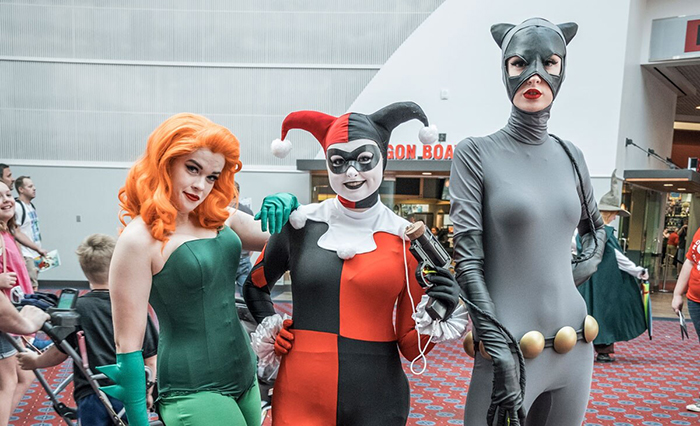 Three people in front of a cinema in Halloween costumes cat clown and a ivy woman