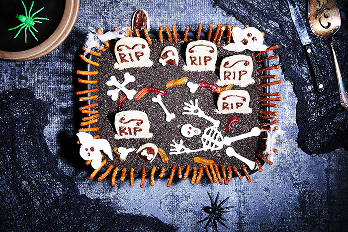 Halloween cake ideas black graveyard cake with skeletons on a black table
