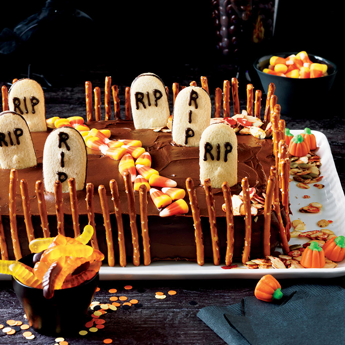Halloween cakes graveyard surrounded with salty sticks and rich decoration