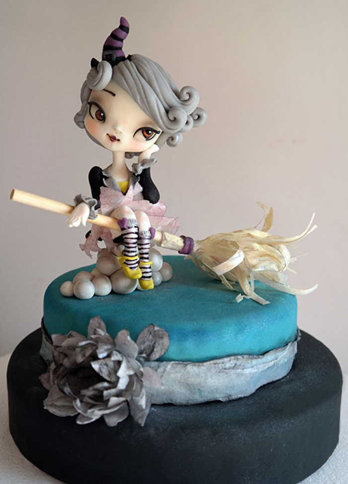 Cute halloween witch cake in blue witch on a broom with a big grey flower
