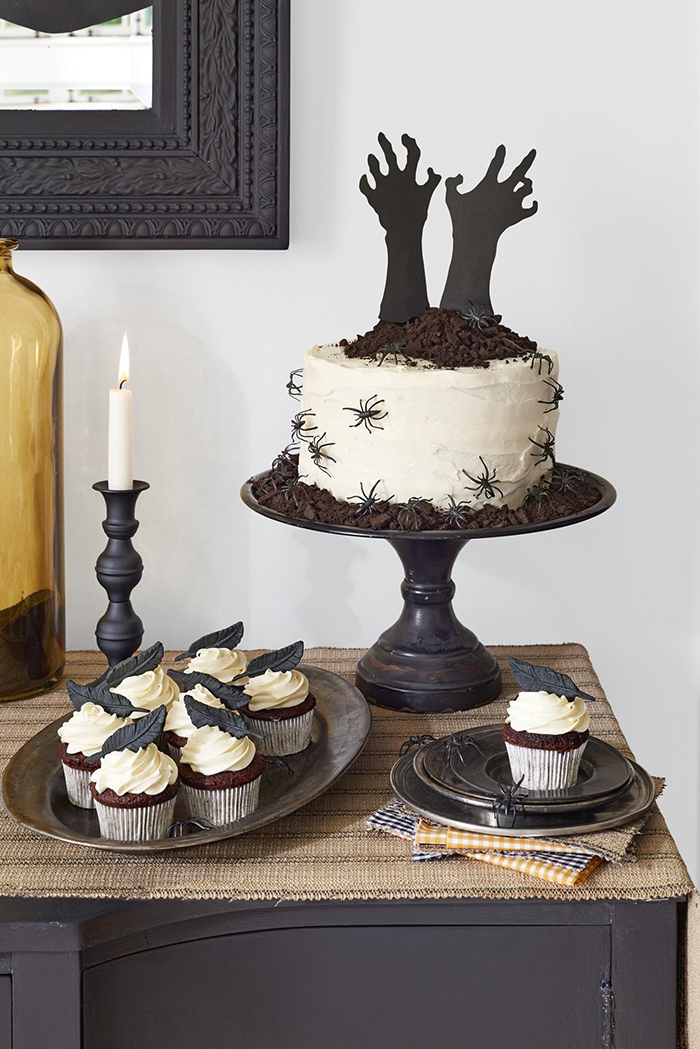 Halloween cakes ideas white cake with hands sticking out and spiders on a table with muffins and a candle