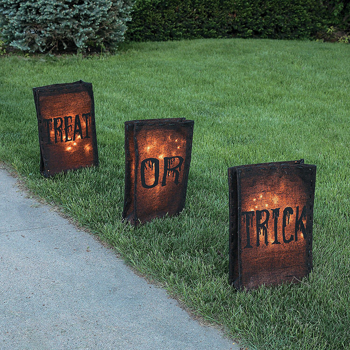 Halloween decor ideas fake outdoor fire baskets on a grass lawn with words on them