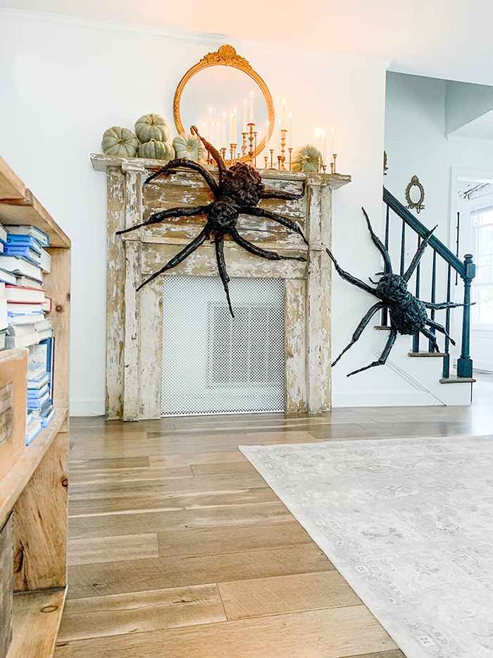Transforming your home for Halloween two giant black spiders in a modern interior on a vintage fireplace