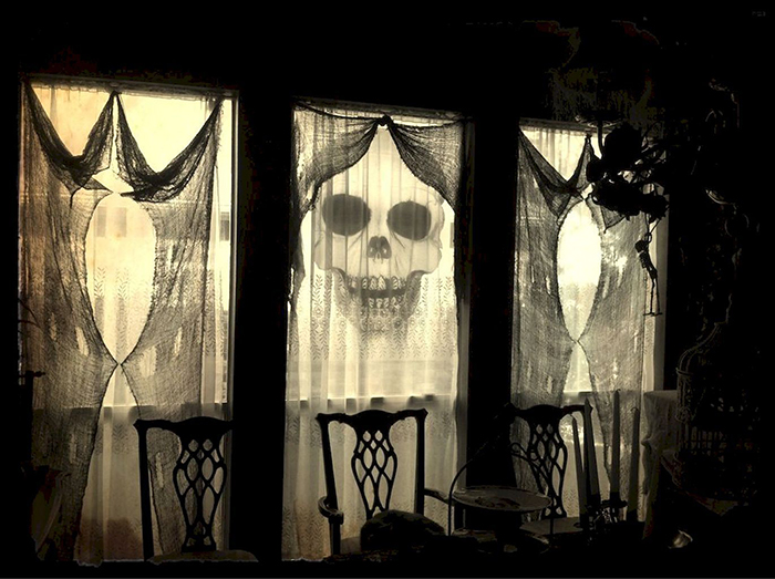 Transforming your Home for Halloween spooky window decor old curtains and a skull