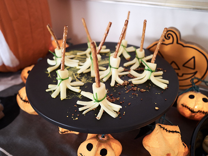 Halloween treat witch broom cheese treat on a black platter