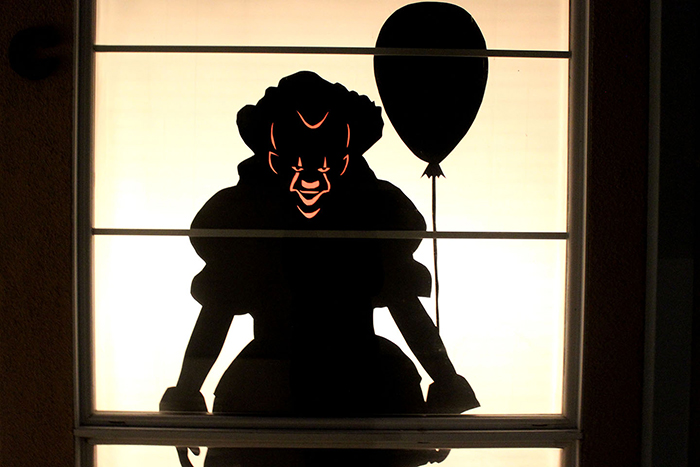Halloween window decor idea spooky black clown with a balloon