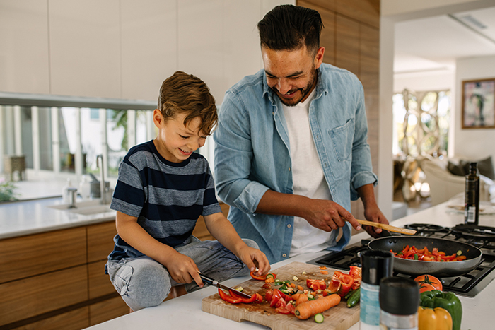 new hobbies a man and a boy cooking together at home chopping vegetables and smiling