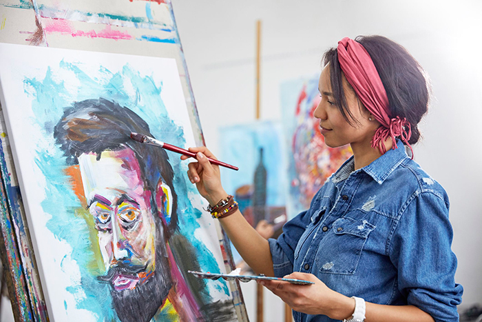 best new hobbies woman in denim jacket painting a man in different colours