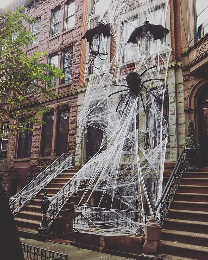 Giant spider web at the exterior of a home with bats and a big black spider