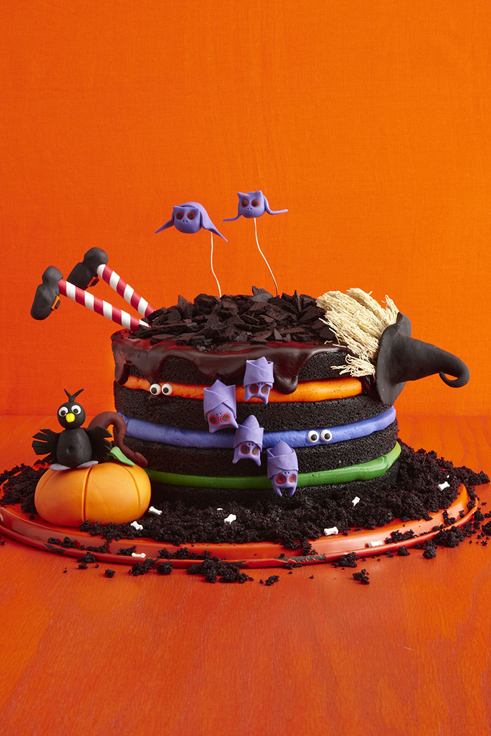 Witch halloween cake with colorful layers and purple bats on a bright orange background