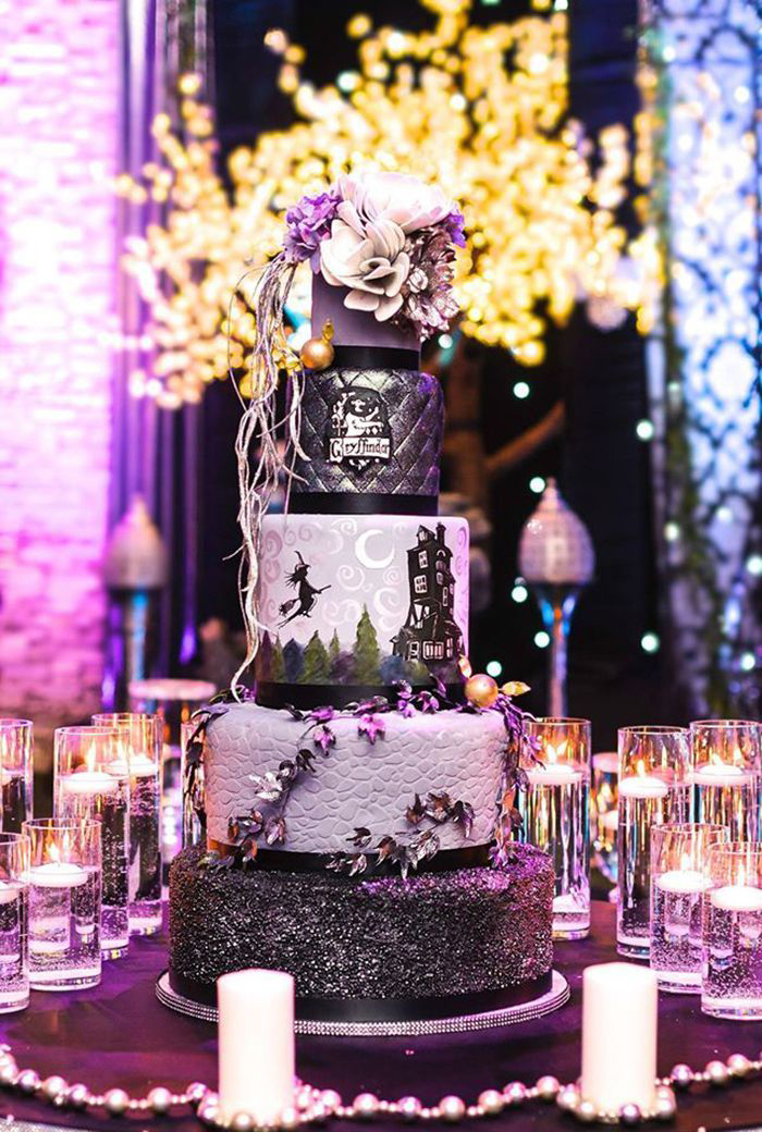 Purple and black witch halloween cake at a party with floral decorations