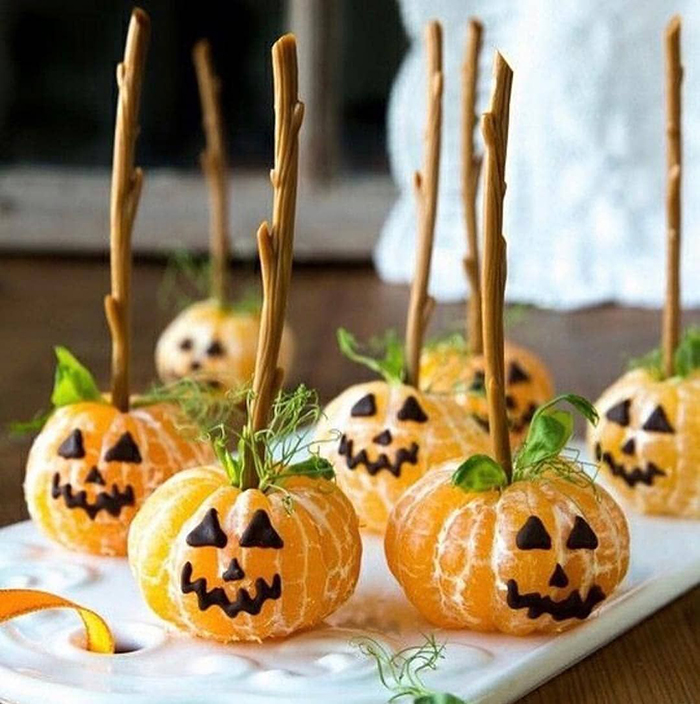 fruity pumpkin treats tangerines with chocolate faces on sticks