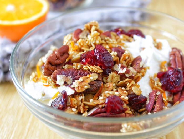 granola with pecans and cranberries in a glass bowl with milk and seeds